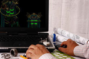 Engineer at Computer with Drawings